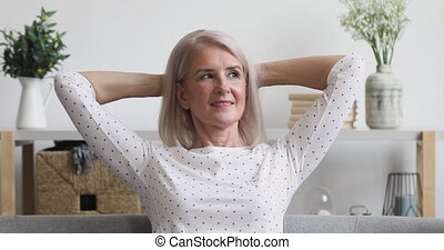 Pleasant middle aged woman relaxing on comfortable sofa at home.