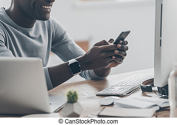 Pleasant moments. Close-up of handsome young African man typing a message on the phone and smiling while sitting at the desk in creative office