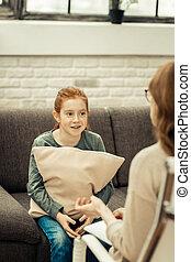 Pleasant nice girl sitting with a cushion