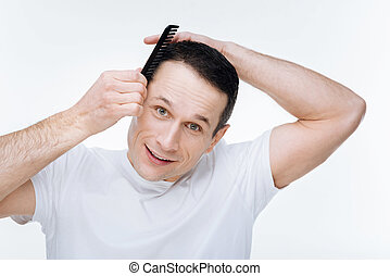 Pleasant nice man holding a comb