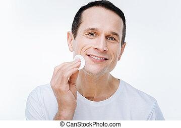 Pleasant nice man holding a cotton pad