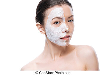 Pleasant nice woman making a facial mask