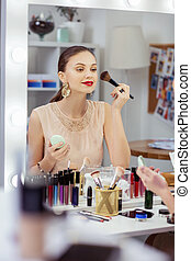 Pleasant nice young woman applying decorative cosmetics