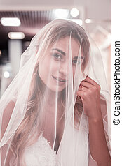 Pleasant nice young woman touching her veil
