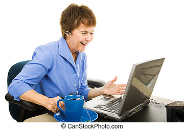 Mature business woman chatting on her blue tooth and looking at her laptop computer. Isolated on white.