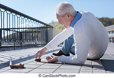 Pleasant pensioner having health problem outdoors - Facing...