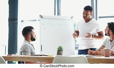 Pleasant positive male colleagues discussing their project -...