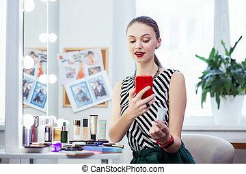 Pleasant pretty woman taking a photo of her cream