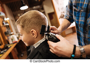 Pleasant professional barber using haircutting machine - New...