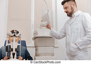 Pleasant professional ophthalmologist choosing the regime