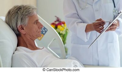 Pleasant retired man signing medical papers - Sign the...