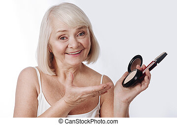 Pleasant retired woman holding face powder and mascara