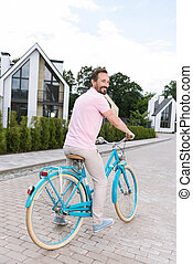 Delighted nice man riding his bike