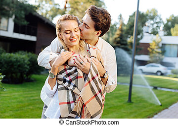 Pleasant romantic man kissing his girlfriend in the cheek