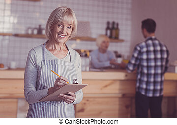 Pleasant satisfied woman standing and making notes.