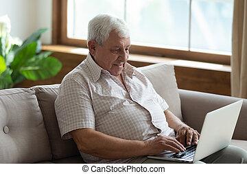 Pleasant senior 70s man sitting on sofa with computer.