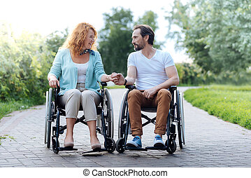 Pleasant senior couple sitting in the wheelchairs outdoors
