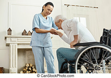 Pleasant senior man holding caregivers hand