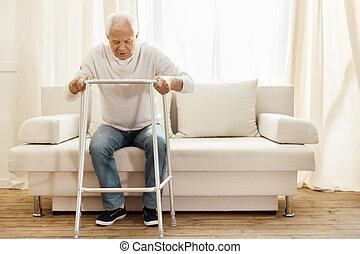 Pleasant senior man leaning on the walker