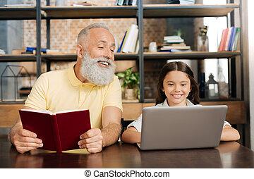 Pleasant senior man looking at her granddaughters laptop screen