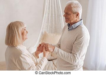 Pleasant senior man looking at his wife