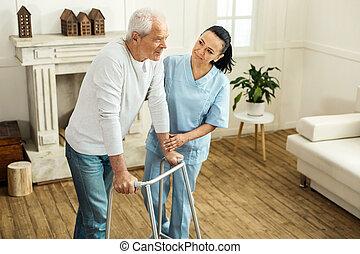 Pleasant senior man using walking equipment