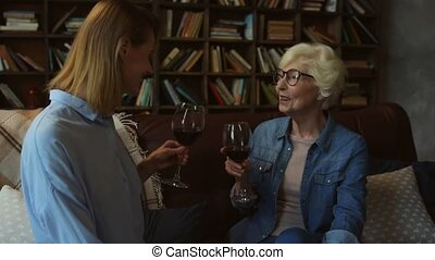 Pleasant senior mother and her daughter drinking wine at...