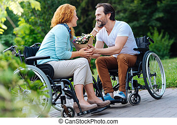 Pleasant senior wheelchaired couple resting in the park