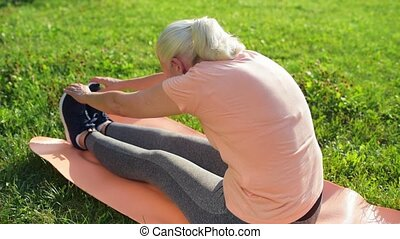 Pleasant senior woman doing sport exercises in the park