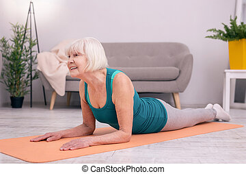 Pleasant senior woman exercising muscles of her neck