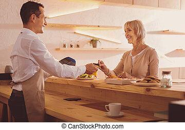 Pleasant senior woman giving bank card to barista