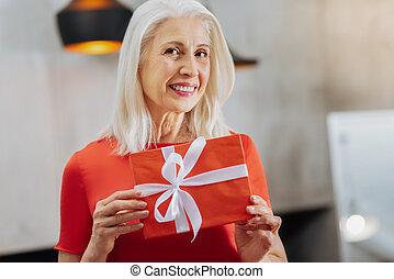 Pleasant senior woman holding a present box