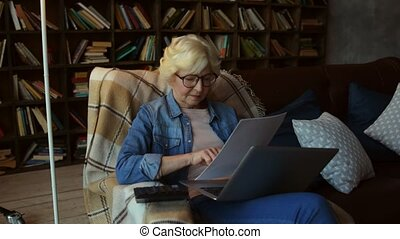 Pleasant senior woman making calculations to secure her...