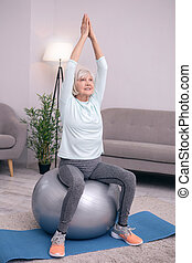 Pleasant senior woman sitting in tree pose on exercise ball