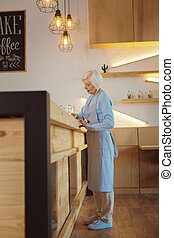 Pleasant senior woman standing at the counter