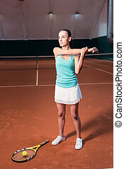 Pleasant slim woman preparing to play tennis.