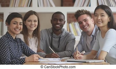 Pleasant smiling mixed race students sitting at table in ...