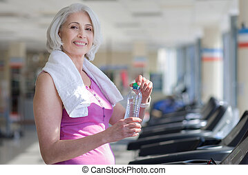 Pleasant smiling senior woman drinking water after fitness.
