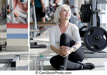 Pleasant smiling senior woman resting in a gym.