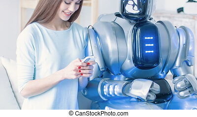 Pleasant smiling woman sitting on the couch with robot