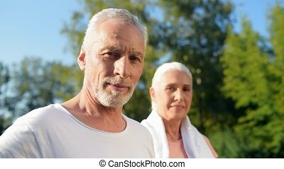 Pleasant sporty eldelry couple standing in the park