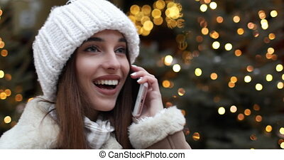 Pleasant Talk in Christmas Time - Smiling girl dressed in...