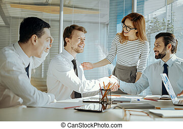 Pleasant team leader reconciling her colleagues during meeting