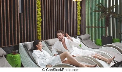 Pleasant unshaven man looking at relaxing girlfriend in the...