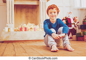 Pleasant upbeat boy sitting near Chimney on Christmas Eve