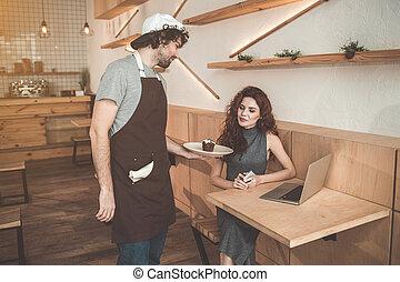 Pleasant waiter giving sweet dessert to client