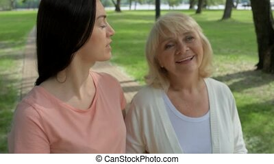 Pleasant woman and her senior mother walking in the park