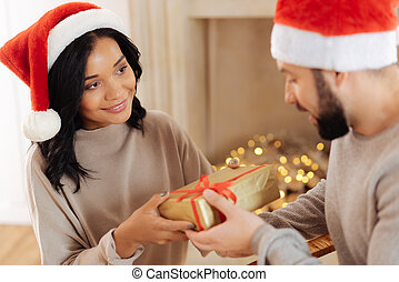 Pleasant woman giving Christmas present to her husband