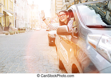 Pleasant woman greeting someone from the car window