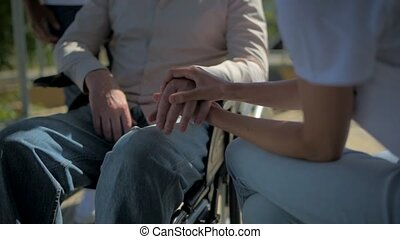 Pleasant woman holding hand of a wheelchaired man